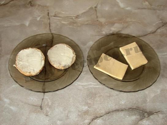 разрежем булочки пополам и намажем маслом, сыр нарезаем ломтиками