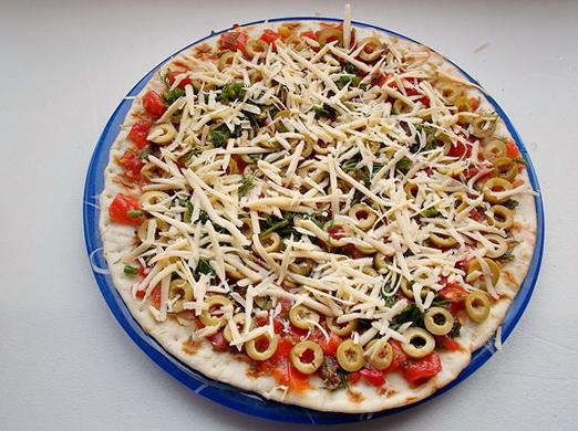 посыпаем пиццу тёртым сыром и укропом