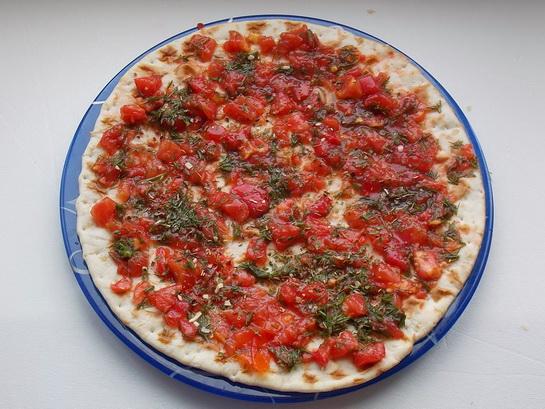 распределяем томатный соус по коржу для пиццы